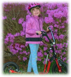 Diana standing on scooter in front of azalea bush